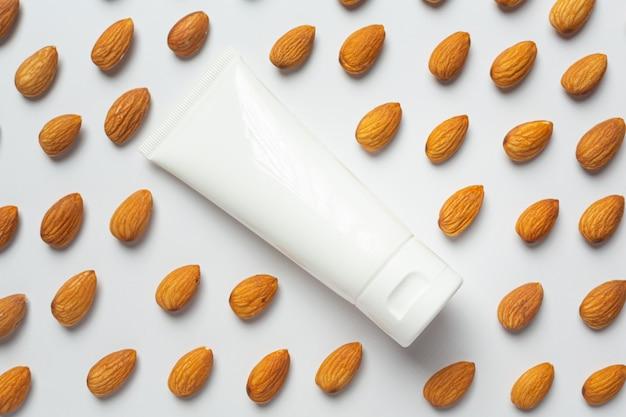 Crema hidratante corporal de almendras sobre fondo blanco.