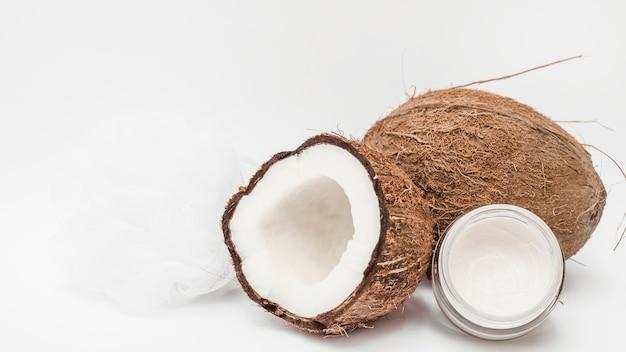 Crema hidratante; loofah y coco en superficie blanca