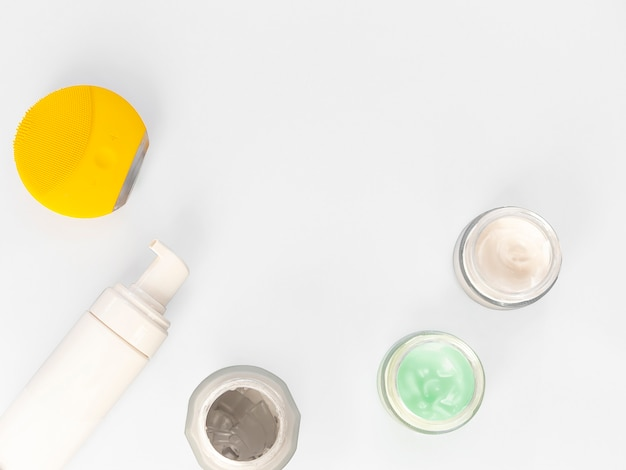Crema higiénica cosmética de la dermatología con el producto del skincare en el tarro de cristal en el fondo blanco.