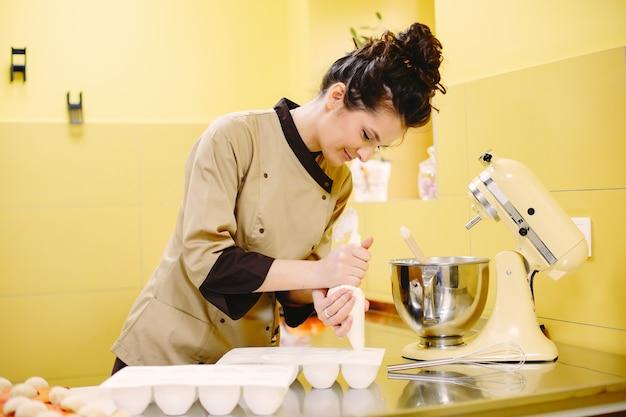 Crema en manga pastelera. señora con una herramienta para hornear.