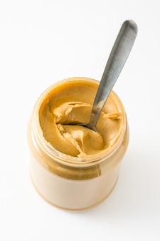 Crema de maní cremosa y cuchara aislado sobre superficie blanca