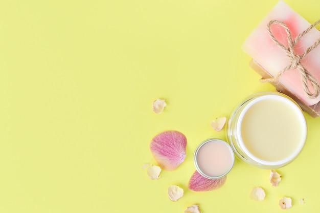 Crema de manos, bálsamo labial y jabón sobre fondo amarillo.