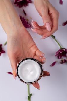 Crema y manos femeninas y flores.