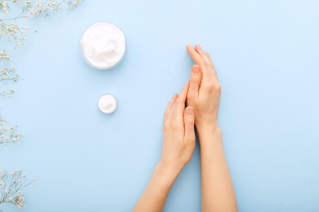Crema de manos hidratante para el cuidado de la piel en manos femeninas sobre fondo de color azul pastel.
