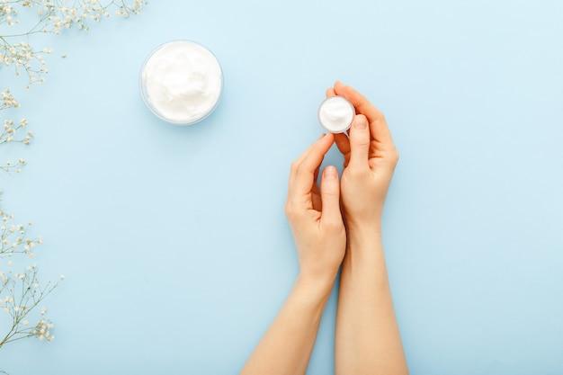 Crema de manos, manos femeninas aplicando cosméticos cremas naturales orgánicos sobre un fondo de color azul pastel.