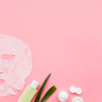 Crema para la piel de aloe vera; hoja de loción y papel mascarilla sobre fondo rosa