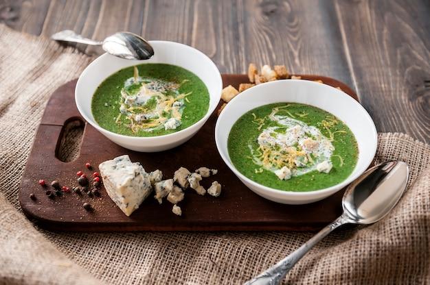 Crema verde de espinacas y brócoli. con la adición de parmesano y queso azul con picatostes. una superficie de madera.