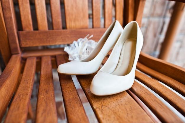 Crema zapatos de novia de novia en silla de madera