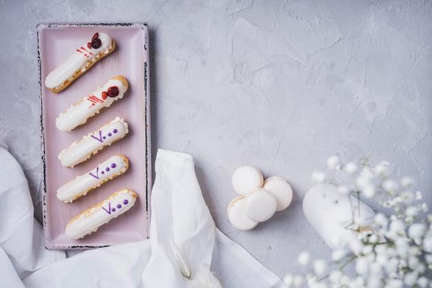 Cremas eclairs con macarrones y jarrón de flores de aliento