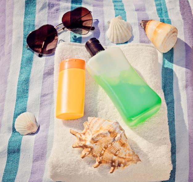 Cremas de protección solar y gafas sobre fondo azul.