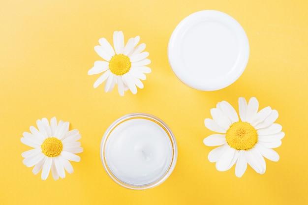 Cremas en tarros cosméticos y margaritas en composiciones de bodegones. concepto de boticario. colores neutros. vista plana, vista superior.