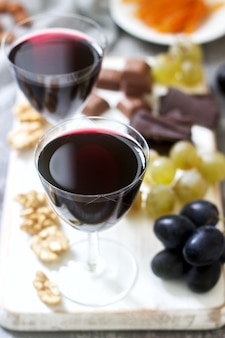 Creme de cassis licor casero servido con uvas, nueces y chocolate