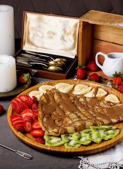 Crepe con salsa de chocolate y fresas en rodajas, kiwi y plátanos