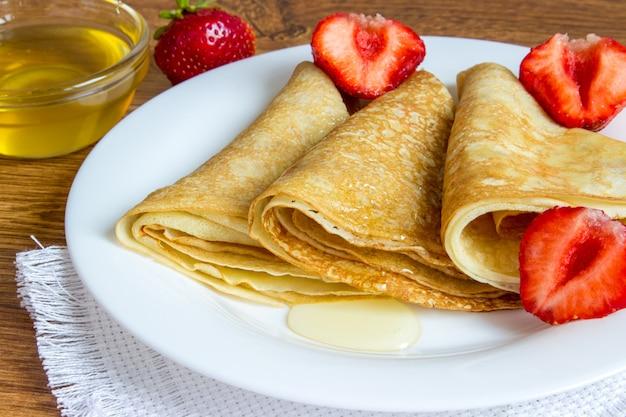 Crepes apiladas con sirope de fresa y miel.
