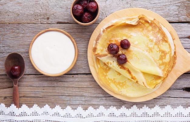 Crepes (blini) y miel sobre fondo de madera, vista superior, espacio de copia. crepes finos caseros para el desayuno o el postre.