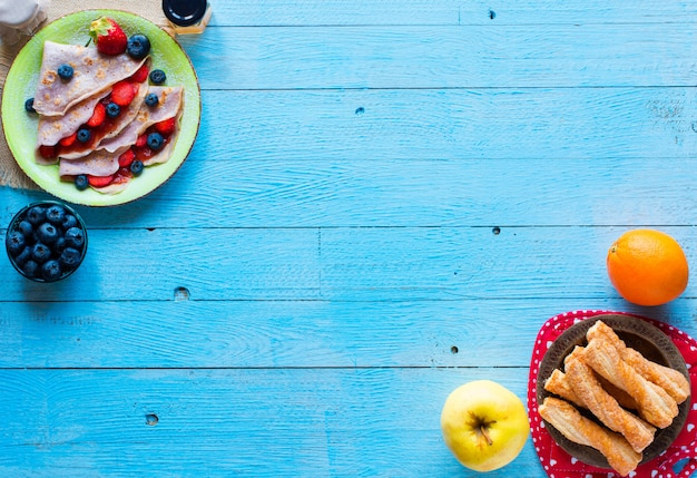 Crepes caseros frescos servidos en un plato con fresas y arándanos en un espacio libre de fondo de madera azul claro para texto.