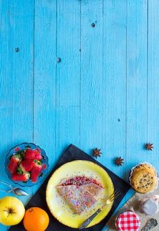 Crepes caseros frescos servidos en un plato con fresas y arándanos sobre un fondo de madera azul claro