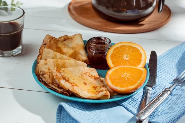 Crepes franceses caseros frescos hechos con huevos, leche y harina, rellenos de mermelada en un plato vintage