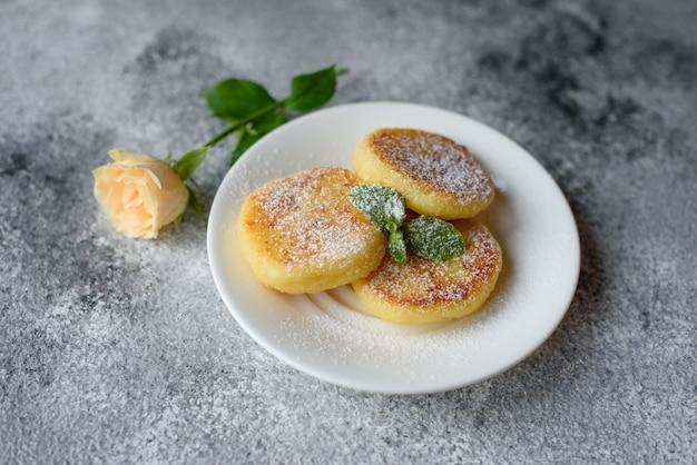 Crepes frescas sabrosas del requesón en una placa blanca en un fondo concreto. desayuno saludable y dietetico.