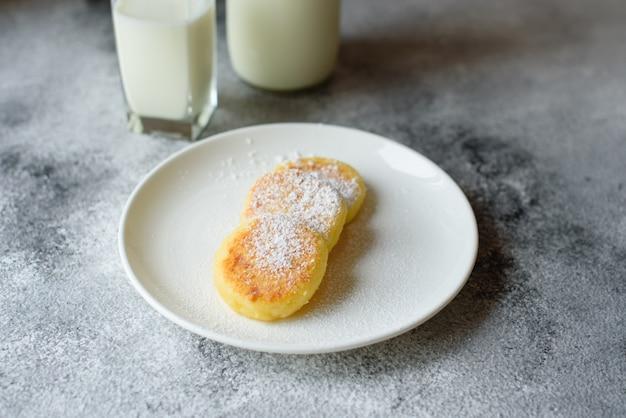 Crepes frescas sabrosas del requesón en una placa blanca con un vidrio de leche en un fondo concreto. desayuno saludable y dietetico.