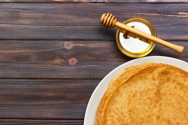 Crepes fritas con la miel en la tabla de madera vieja.