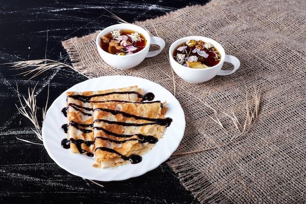 Crepes en un plato blanco con sirope de chocolate y té.