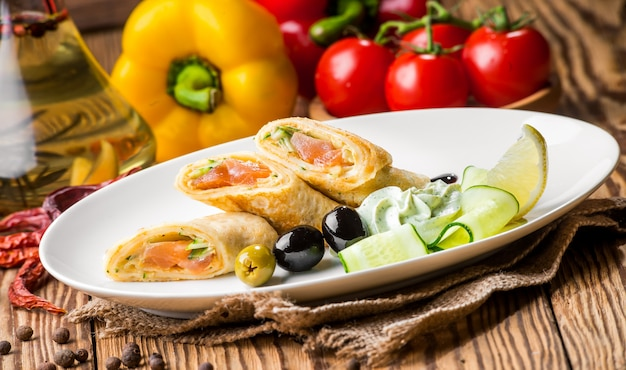 Crepes con salmón ahumado en un plato blanco