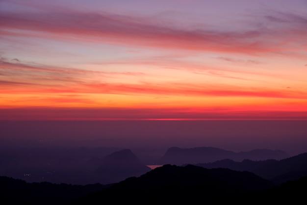 Crepúsculo rosa claro y colores morados muy bien. refleja las vistas montañas y niebla por la mañana.