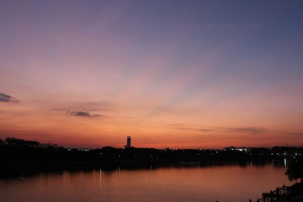 Crepúsculo de la silueta con la reflexión del lago en el fondo del paisaje de la superficie del agua