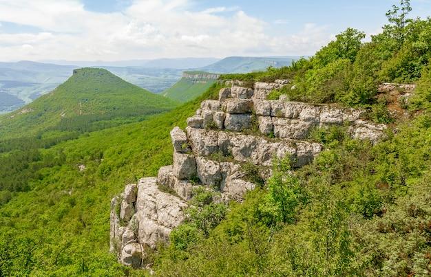 Cresta de piedra con una plataforma para ver el paisaje y las montañas en forma de pirámide.