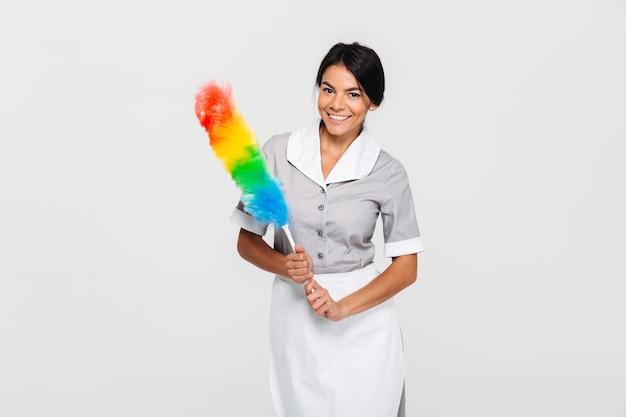 Criada alegre en uniforme con plumero colorido mientras está de pie