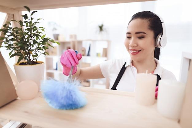 Criada filipina limpiando con plumero.