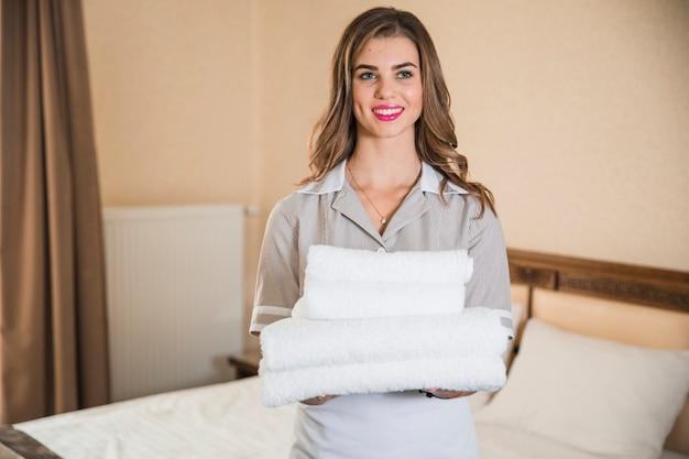 Criada joven sonriente que sostiene la pila blanca de toallas que se colocan delante de cama
