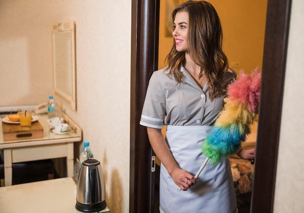 Criada joven sonriente que sostiene el plumero en la mano que se coloca cerca de una puerta abierta en la habitación de hotel