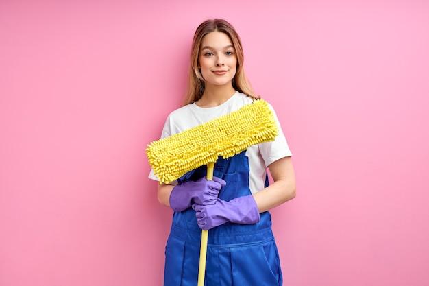 La criada va a limpiar el piso con un trapeador, de pie con guantes de goma posando en la cámara aislada sobre fondo rosa