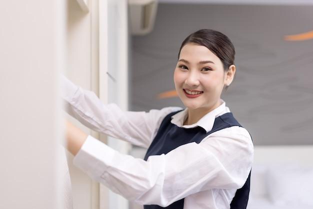 Criada sonriente con albornoz blanco con percha en el armario, el concepto de la empresa hotelera