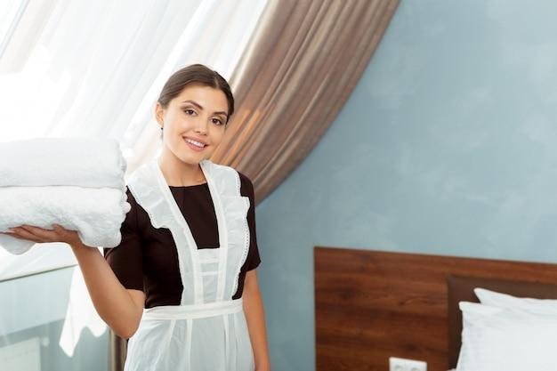 Criada con toallas limpias y frescas durante la limpieza en una habitación de hotel