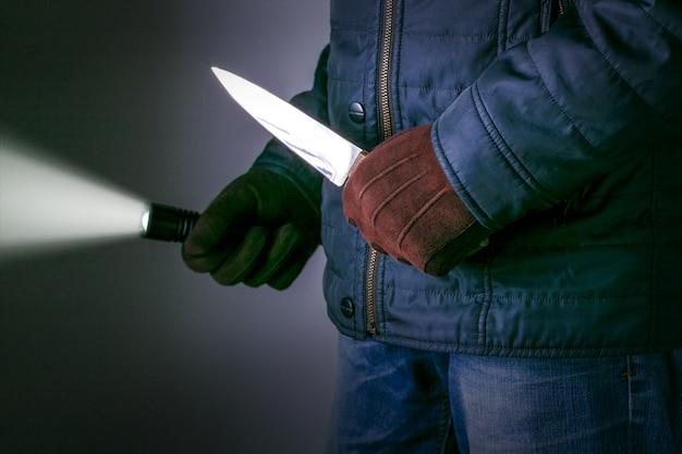 Un criminal con un arma de cuchillo amenaza con matar. conceptos del crimen conceptos de robo