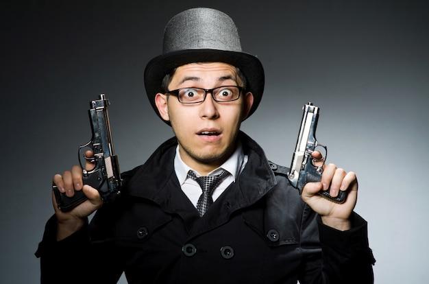 Criminal en saco negro sosteniendo hasgun contra gris.