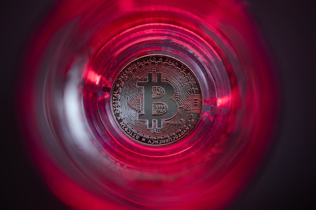 Criptomoneda cayendo al fondo. fondo rojo y luz de fondo morada. bitcoin en un vaso con