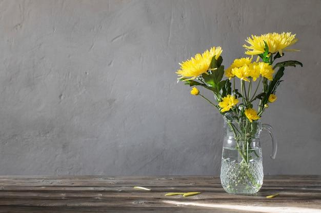 Crisantemo amarillo en jarra de vidrio sobre fondo antiguo muro