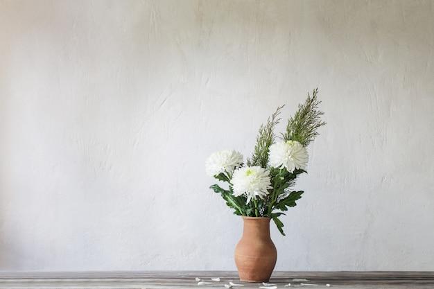 Crisantemo blanco en jarra en la pared vieja de fondo
