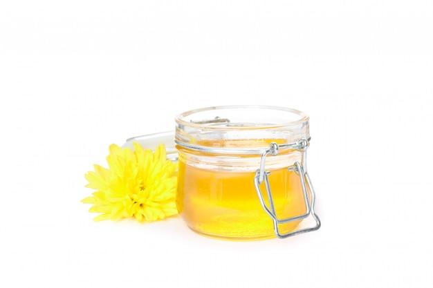 Crisantemo y tarro de cristal con miel aislado en blanco