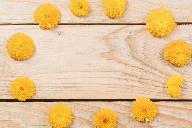 Crisantemos amarillos sobre madera