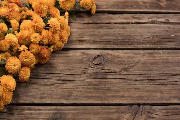 Crisantemos naranjas sobre madera vieja