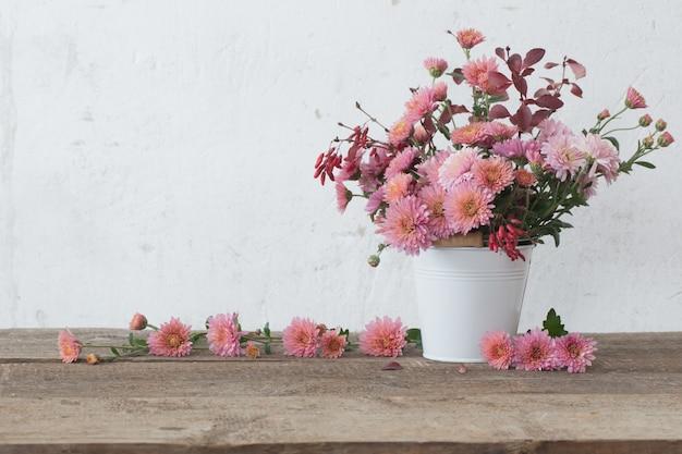 Crisantemos rosados en la mesa de madera antigua