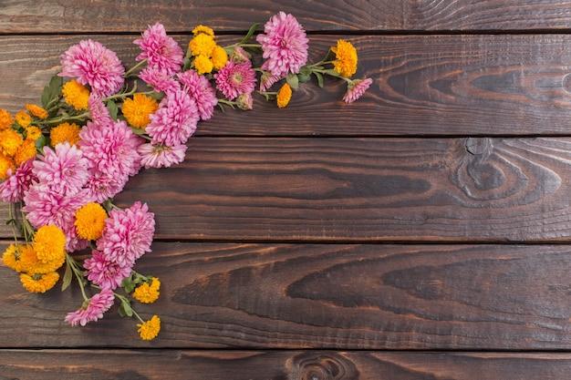 Crisantemos rosados y naranjas sobre madera oscura