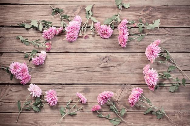 Crisantemos rosados sobre fondo de madera oscura