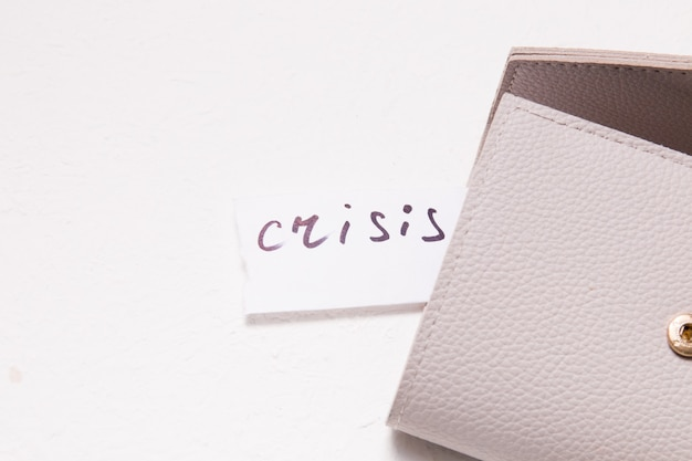 La crisis de inscripción en un pequeño trozo de papel blanco sobresale del bolsillo de la billetera