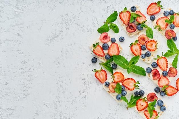 Crispbread de la subida con concepto colorido de las bayas y de las frutas en la opinión superior del espacio en colores pastel de la copia del fondo